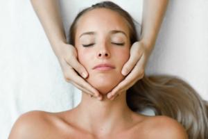 Une femme en train de recevoir un traitement d'ostéopathe au niveau de sa mâchoire