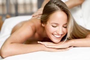une femme blonde, souriante, couchée sur le ventre, en train de recevoir des soins