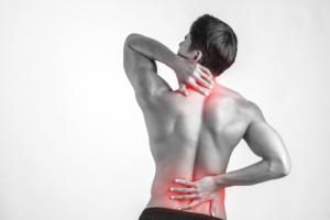 Vue d'un homme de dos, avec des douleurs dans les lombaires et la nuque, avec les mains au niveau de ses douleurs